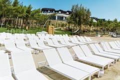 Пристаньте к берегу с белыми sunbeds в ряд на песчаном пляже Стоковые Изображения RF