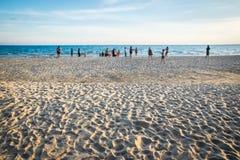Пристаньте к берегу с запачканными людьми на белом времени захода солнца песка Стоковое Фото