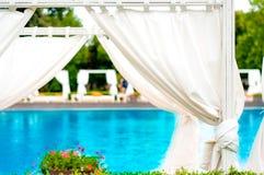 Пристаньте передние ослабляя sunbeds к берегу внутри шатра на причудливом бассейне Стоковое Фото