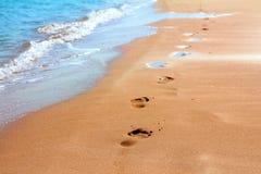 пристаньте песок к берегу следов ноги Стоковая Фотография