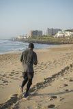 пристаньте рубашки бегунка игрока телефона нот mp3 модели человека кавказской пригодности jogging слушая спорт к берегу t мыжской Стоковое Изображение