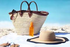 Пристаньте сумку к берегу и шляпу, солнечные очки и лосьон солнцезащитного крема Стоковые Изображения