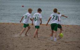 Пристаньте футбольную команду к берегу мальчиков играя на песке Стоковое Фото