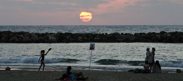 Пристаньте ходоков к берегу silouhetted на заходе солнца в Тель-Авив, Израиле Стоковое Фото