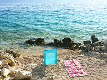 Пристаньте шезлонг и пляжный полотенце к берегу на Pebble Beach морем с малыми волнами Стоковое фото RF