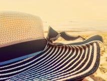 Пристаньте brim к берегу шляпы широкий большой на пляже на заходе солнца стоковые изображения rf