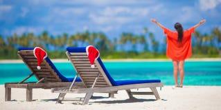 Пристаньте loungers к берегу с красными шляпами и молодой женщиной Санты Стоковые Фотографии RF