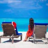 Пристаньте loungers к берегу с красными шляпой и молодой женщиной Санты Стоковые Фото