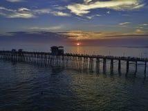 Пристань берега океана на заходе солнца Стоковые Изображения