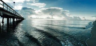 Пристань и океан с пасмурным голубым небом стоковые изображения