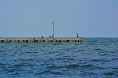 Пристань и рыболовы моря на awindy день стоковая фотография rf