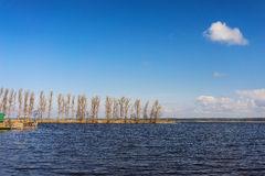 Пристань на озере в древесинах на береге на солнечный весенний день Стоковая Фотография