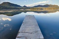 Пристань на озере на предпосылке захода солнца в ясном летнем дне Теплый вечер лета на доке Фантастичные взгляды озера стоковое фото