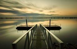 Пристань под облаками на восходе солнца Стоковая Фотография RF