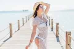 Пристань представления девушки на море в соломенной шляпе и солнечных очках Женщина в сексуальном купальнике на тропическом пляже Стоковые Изображения RF