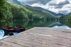 Пристань с деревянными шлюпками строки на озере Biogradskoe Небо с отражением солнца и облаков Горы Bjelasica, Kolasin, Biogradsk стоковая фотография