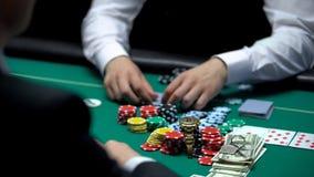 Пристрастившийся игрок в покер идя все-в, держащ пари обломоки, деньги и свойство, безумные стоковое фото rf