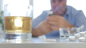 Пристрастившийся человек делая опасные таблетки алкоголя и взятия напитка дыма комбинации стоковое изображение