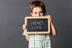 Пристыженный мальчик preschool сообщая о головных вош на школе Стоковые Изображения