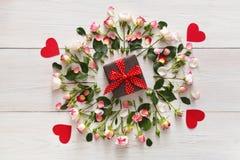 Присутствующая коробка в розовой естественной рамке роз на белой деревенской древесине стоковые фото
