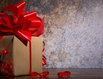 Присутствующая коробка с красной лентой смычка и shinny меньшие сердца на деревянной деревенской доске на день Святого Валентина стоковые изображения rf