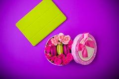 Присутствующая коробка с macaroons цветков и предпосылкой таблетки фиолетовой с влюбленностью Стоковые Изображения RF