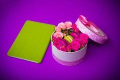 Присутствующая коробка с macaroons цветков и предпосылкой таблетки фиолетовой с влюбленностью Стоковое фото RF