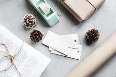 Присутствующая подарочная коробка с конусом сосны на деревянной предпосылке Стоковое фото RF