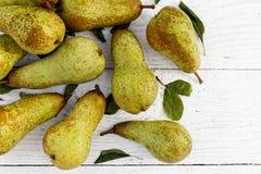 Притухните груши fetel с листьями на белизне покрашенной деревянной сверху Стоковые Изображения RF