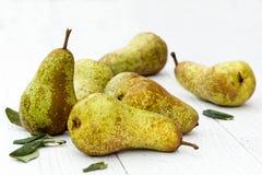 Притухните груши fetel с листьями на покрашенной белизне деревянной Стоковое Изображение RF