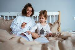 Притяжка мамы и дочери в кровати стоковое фото rf