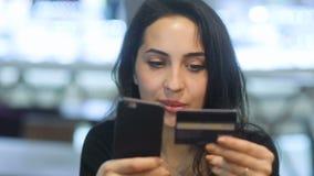 Прифронтовой крупный план усмехаясь молодой элегантной привлекательной девушки с глубоко - коричневый цвет наблюдает в черном пла сток-видео