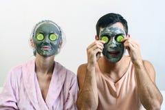 Прифронтовой портрет пожененной пары с масками глины на его стороне и огурцов перед им Спа на дому прикладывать политуру кожи вни Стоковая Фотография