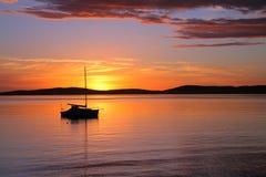 причаленная шлюпка плавающ восход солнца Стоковое Изображение RF