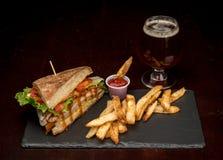 Причудливое стекло пива с половинным сандвичем клуба с фраями Стоковое фото RF