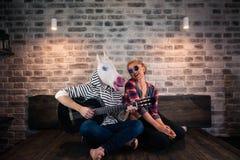 Причудливый человек в комичной маске и причинных одеждах играя музыку на гитаре стоковая фотография rf