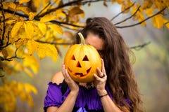 Причудливая женщина на хеллоуине в лесе, держа в тыкве рук с высекаенной стороной Стоковое Изображение RF