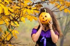 Причудливая женщина на хеллоуине в лесе, держа в тыкве рук с высекаенной стороной Стоковая Фотография