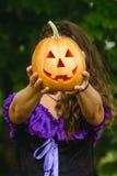 Причудливая женщина на хеллоуине в лесе, держа в тыкве рук с высекаенной стороной Стоковые Изображения RF