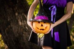 Причудливая женщина на хеллоуине в лесе, держа в тыкве рук с высекаенной стороной Стоковое Изображение