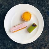 Причудливые миниатюрные печенья eclair, пирог лимона, пирог matcha на плите Стоковое Изображение RF
