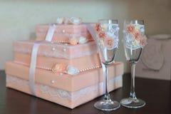 2 причудливых wedding стекла с украшенной коробкой на предпосылке Цвет моркови Стоковое Изображение