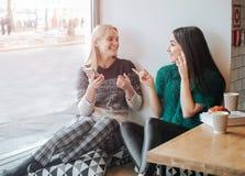 Приятельство и технология 2 милых девушки используя smartphones пока выпивающ чай или кофе на кафе стоковые фотографии rf
