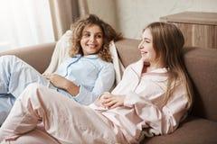 Приятельство перед отношением Красивые европейские девушки лежа на софе в уютном nightwear, говоря и имея потеху Стоковые Фотографии RF