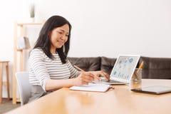 Приятная азиатская женщина работая в офисе Стоковые Фото