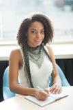 Приятная девушка сидя на таблице Стоковая Фотография RF