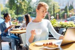 Приятная женщина держа чашку кофе пока читающ Стоковое Изображение