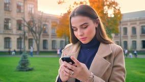 Приятная кавказская женщина стоит прямой, сфокусированный на ее приборе и перечисляет холодок телефона, на открытом воздухе, днев акции видеоматериалы