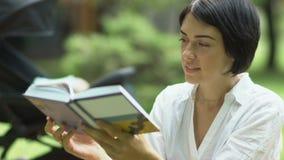 Приятная мать читает книгу акции видеоматериалы