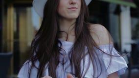 Приятная молодая женщина держит чашку кофе в ее руках сидя в кафе улицы акции видеоматериалы